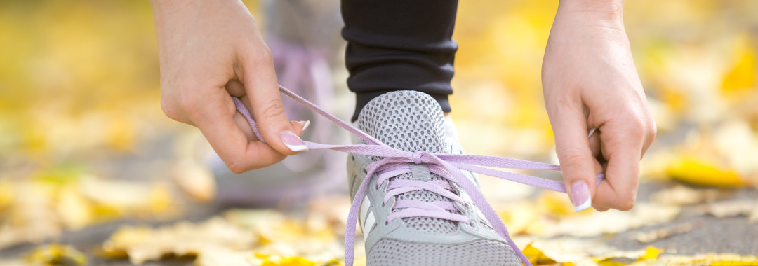Hands tying trainers shoelaces on the autumn pave, full of yellow leaves. Concept photo, horizontal, closeup