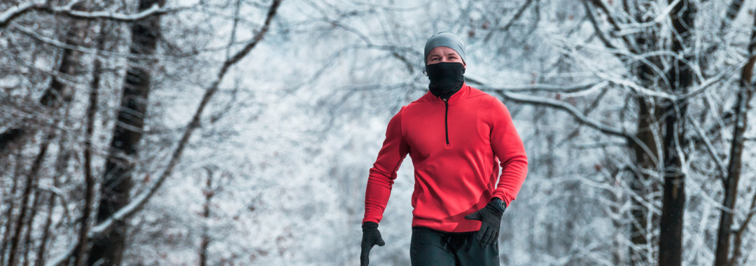 Winter running exercise, runner on road in the snowy forest