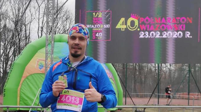 Biegacz Dariusz Mazek w błękitej bluzie z medalem 40. Półmaratonu Wiązowkiego